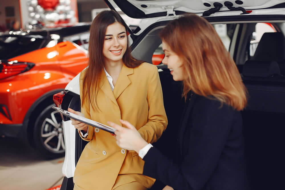 A car dealer speaking to a customer in front of cars